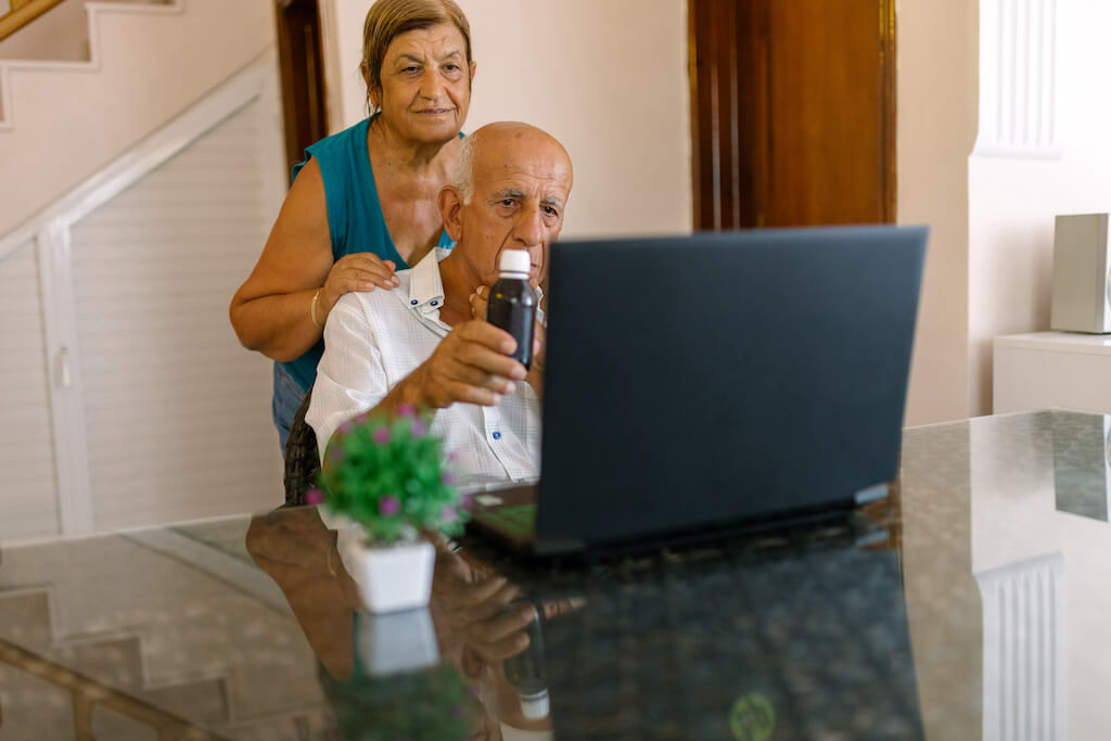 elderly man and wife using laptop together